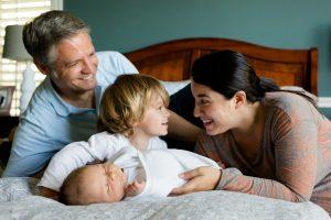 loving family of four on bed family estate plan